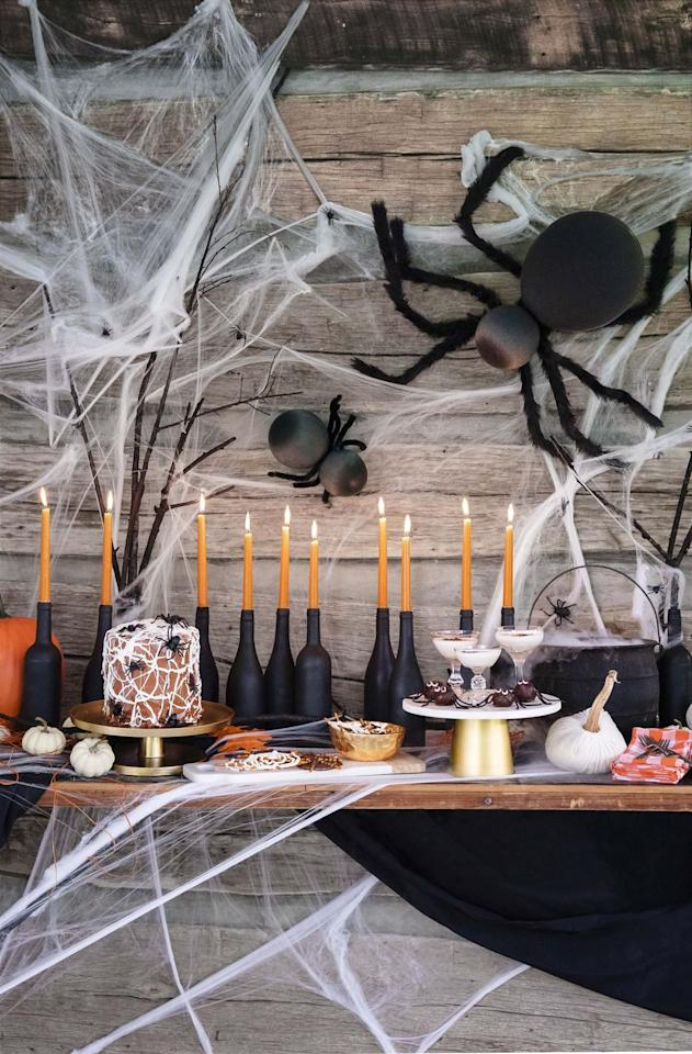 """<p>Add a spooky balloon spider to your door for a not-too-creepy addition to your decor.</p><p><strong>Make the body:</strong> Blow up one large black balloon for the body and one smaller black balloon for the head. Tie the two balloon knots together to form the spider.</p><p><strong>Make the legs: </strong>Wrap eight lengths of unfurled wire hanger or 12-gauge craft wire with black faux fur, holding in place with hot-glue. Twist ends of four lengths together, creating bundles of legs. Repeat with remaining four lengths.</p><p><strong>Assemble the spider: </strong>Wrap a black pipe cleaner around twisted ends of leg bundles. Wrap pipe cleaner around """"neck"""" of spider where balloons are tied together. Wrap fishing wire around leg to hang.</p><p><a class=""""body-btn-link"""" href=""""https://www.amazon.com/Shannon-Luxury-Faux-Grizzly-Black/dp/B07FFTH79R/ref=sr_1_36?tag=syn-yahoo-20&ascsubtag=%5Bartid%7C10050.g.22350299%5Bsrc%7Cyahoo-us"""" target=""""_blank"""">Shop Faux Fur</a></p>"""