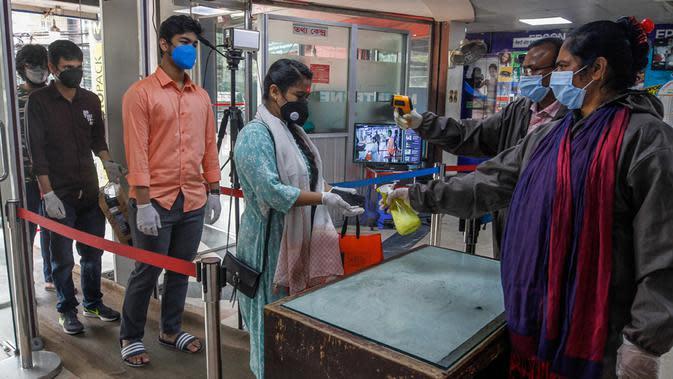 Pegawai menyemprotkan cairan pembersih tangan kepada seorang wanita di sebuah pasar di Dhaka, Bangladesh, Senin (11/5/2020). Jalan-jalan utama Dhaka kembali ramai sehari setelah toko-toko dan pasar kembali dibuka secara terbatas mengikuti aturan pemerintah. (Xinhua/Stringer)