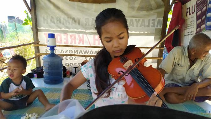 Jawa Nur Alam (13), gadis yang piawai memainkan alat musik biola yang videonya sempat ramai di media sosial. (Foto: Liputan6.com/Dian Kurniawan)