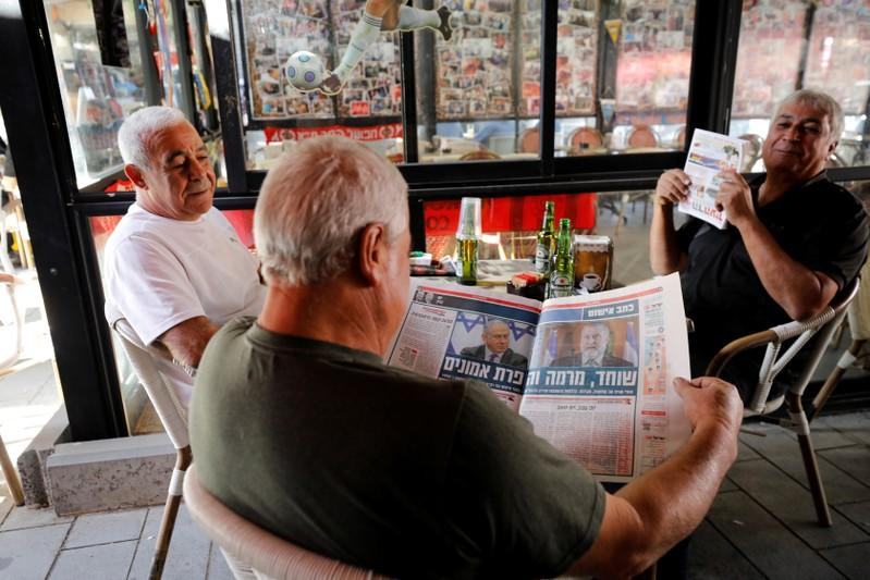 An Israeli man reads a local daily newspaper as he sits in a coffee shop in Ashkelon