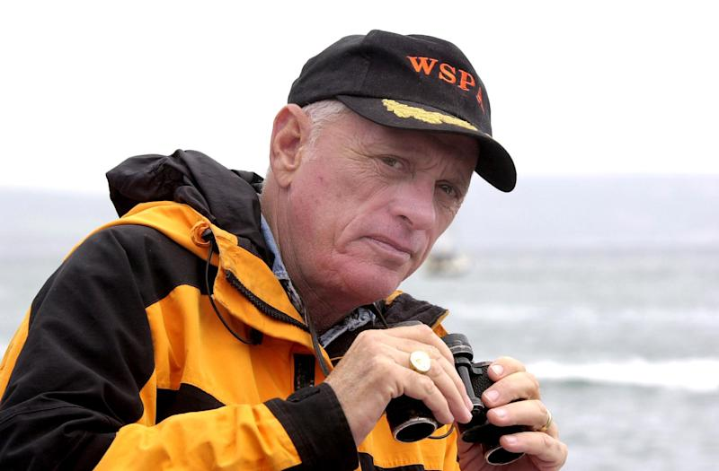 Ric O'Barry wears a black cap and holds binoculars. He is standing in front of the ocean.
