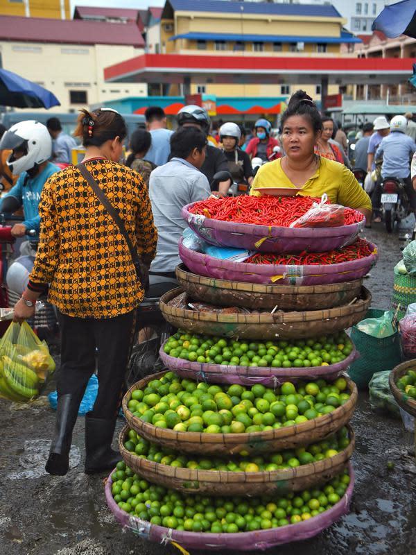 Seorang wanita mendorong troli penuh limau dan cabai di sebuah pasar di Phnom Penh (24/7/2020). Ibu kota Kamboja ini dipenuhi pasar baik besar maupun kecil. (AFP/Tang Chhin Sothy)
