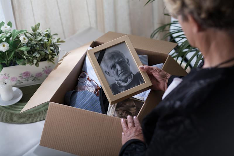 Woman is packing things of her dead husband into a box