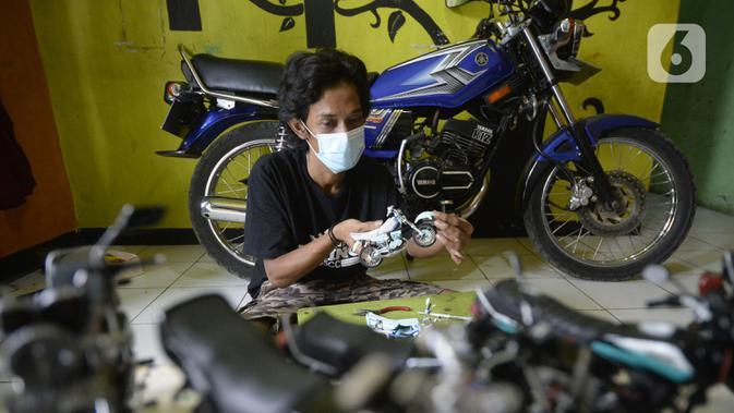 Perajin Wawang Kurniawan (38) menyelesaikan pembuatan miniatur motor RX King di Kelurahan Serua, Ciputat, Tangerang Selatan, Sabtu (17/10/2020). Miniatur dari limbah korek api, pipa plastik, kabel, kaleng minuman, dan kawat itu dijual seharga Rp 400 - Rp 450 ribu per unit. (merdeka.com/Dwi Narwoko)