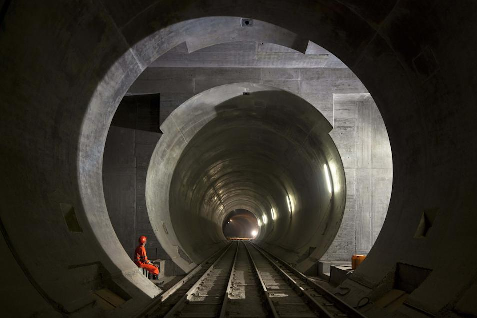 """this Aug. 27, 2010 photo shows a worker taking a break in the shaft of the gate still to be built at the track change between the two tunnels in the Gotthard Base Tunnel's """"Faido"""" section near Faido in the canton of Ticino, Switzerland.. The company in charge of the project says there are only 59 feet (18 meters) left to dig before completing the last section of the new Gotthard Base Tunnel. When it is opened for traffic in 2017, the Gotthard Base Tunnel will supplant Japan's 33.5-mile (53.6-kilometer) Seikan Tunnel as the world's longest _ excluding aqueducts _ and allow millions more tons of goods to be transported quickly through the Alps by rail. (AP Photo/Keystone, Martin Ruetschi) *** NO SALES, NO ARCHIVES ***"""