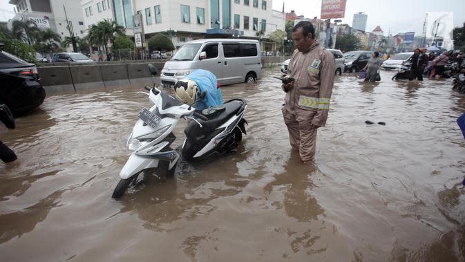 Seorang pengendara memperbaiki motornya yang mogok saat melintasi banjir di Jalan Boulevard Barat Raya, Kelapa Gading, Jakarta, Kamis (15/2). Hujan lebat yang mengguyur Jakarta mengakibatkan sejumlah wilayah terendam banjir. (Liputan6.com/Arya Manggala)