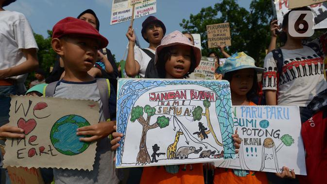 Anak-anak membawa spanduk bertuliskan pesan saat aktivis lingkungan hidup dari berbagai LSM berjalan kaki menuju Taman Aspirasi di Istana Merdeka, Jakarta, Jumat (29/11/2019). Aktivis meminta pemerintah segera mendeklarasikan perubahan iklim yang semakin kritis. (merdeka.com/Imam Buhori)
