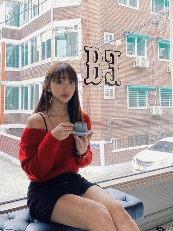 Wanita lulusan American Musical and Dramatic Academy jurusan Dance Theatre ini juga tampak elegan dengan gaya kasual. Saat sedang menikmati secangkir kopi di salah satu kafe di Korea Selatan, ia terlihat menawan dalam balutan busana merah dan hitam. (Liputan6.com/IG/@ditakarang)