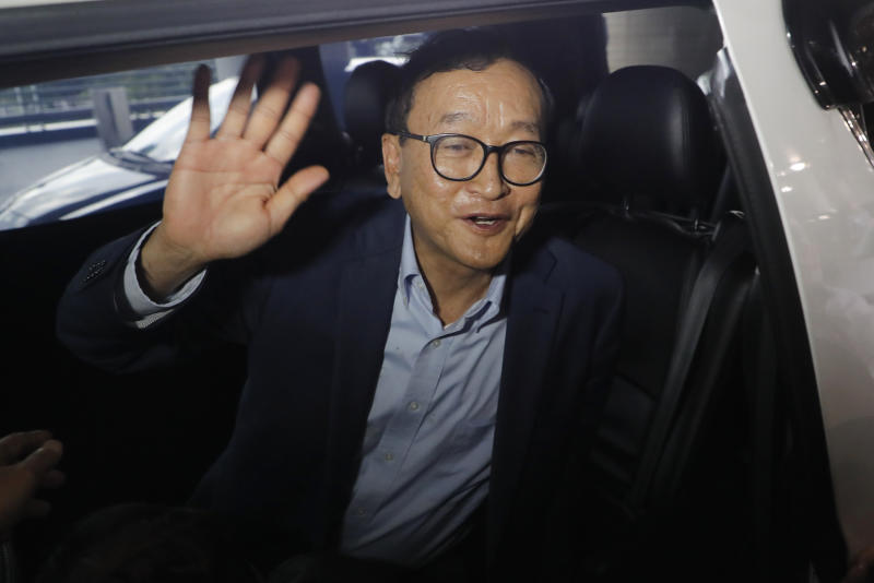 Cambodia's exiled opposition leader Sam Rainsy waves as he gets in a car after arriving at Kuala Lumpur International's Airport in Sepang, Malaysia Saturday, Nov. 9, 2019. Sam Rainsy landed in Kuala Lumpur in a bid to return to his homeland after Thailand had earlier blocked him from entering. (AP Photo/Vincent Thian)