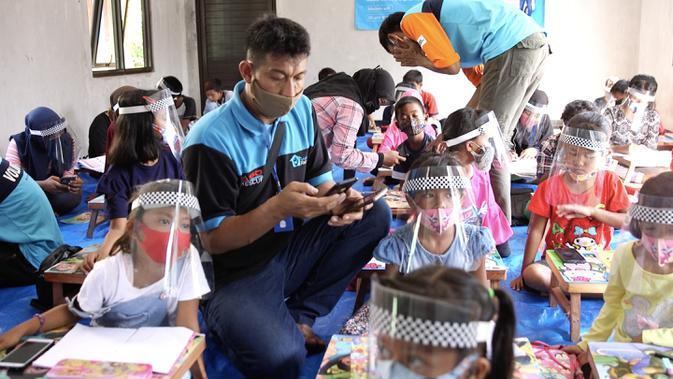 Kepala Program Sekolah Relawan, Abdul Manaf bersama para siswa yang menerima bantuan Mobile Wifi. Sekolah Relawan juga mengajarkan dari awal bagaimana cara mengakses internet untuk belajar online. (Foto: Liputan6.com)