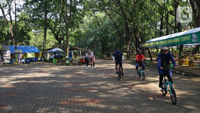 Sejumlah pengunjung menaiki sepeda untuk berkeliling Taman Margasatwa Ragunan, Jakarta, Sabtu (20/6/2020). Ragunan mulai dibuka kembali untuk pengunjung pada Sabtu ini di masa PSBB transisi dengan pembatasan dan penerapan protokol kesehatan yang ketat. (Liputan6.com/Herman Zakharia)