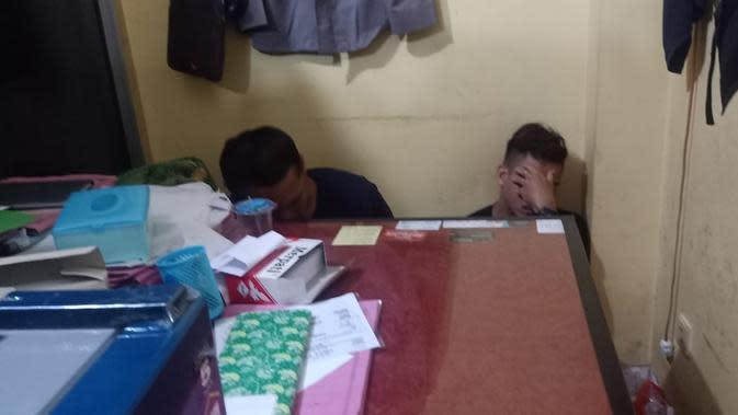 AN dan IW menutup wajahnya saat diamankan oleh Tim Hunter ke Mapolrestabes Palembang (Liputan6.com / Nefri Inge)