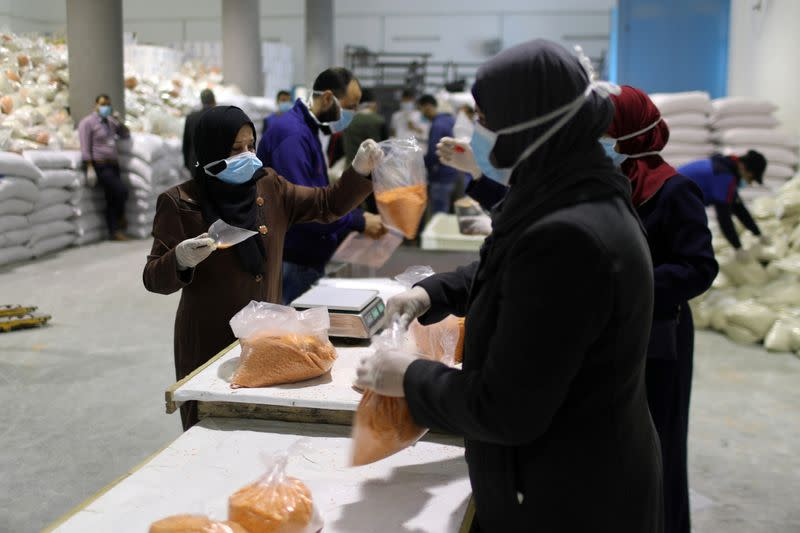 Workers pack food supplies to be distributed and delivered by UNRWA to the homes of Palestinian refugees in the northern Gaza Strip