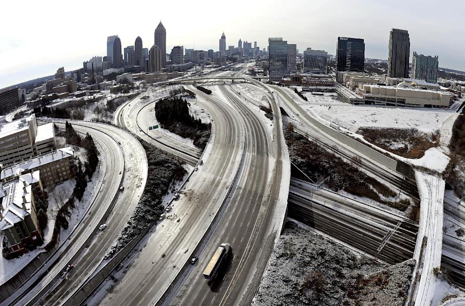"FILE -In this Wednesday, Jan. 29, 2014 file photo, In this aerial photo taken with a fisheye lens looking south toward downtown Atlanta, the ice-covered interstate system shows the remnants of a winter snow storm, in Atlanta. Less than nine days after a storm trapped commuters in cars and children on school buses in metro Atlanta, state officials say they ""overreacted"" to information from federal forecasters and posted incorrect information on giant message boards over freeways. (AP Photo/David Tulis, File)"