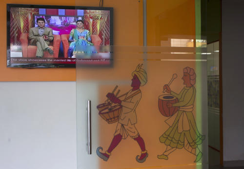 In this July 26, 2013 photo, a talk show episode is displayed on a television at the entrance of the Shagun TV studio in Noida, India. Indians are obsessed with weddings and obsessed with reality television. Now Shagun TV, a new television channel headquartered in a sprawling suburb of India's capital, is hoping it has found a can't-miss idea — merging the two into a 24-hour matrimonial TV station.(AP Photo/Tsering Topgyal)