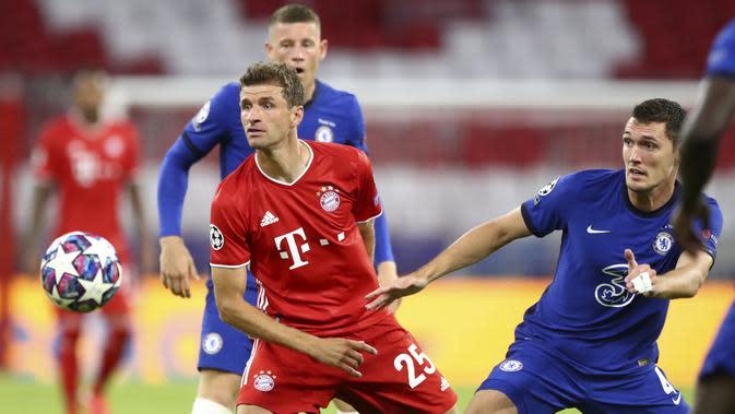 Penyerang Bayern Munchen, Thomas Mueller berebut bola dengan bek Chelsea, Andreas Chistensen pada leg kedua babak 16 besar Liga Champions di Allianz Arena, Jerman (8/8/2020). Munchen menang 4-1 atas Chelsea dan melaju ke perempat final dengan aggregat skor 7-1. (AP Photo/Matthias Schrader)