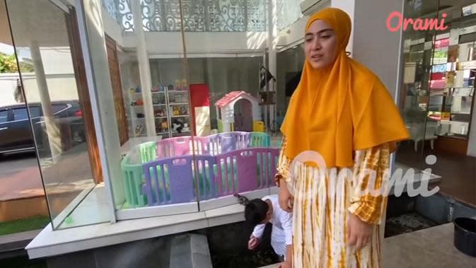 Masih tidak jauh dari mushala, terlihat anak pertama April dan Solmed sedang membersihkan kolam ikan. April mengaku, bahwa putra pertamanya, Sultan Mahmoed Qusyairi lebih suka bersih-bersih dibanding mengerjakan PR. (Youtube/Orami Indonesia)
