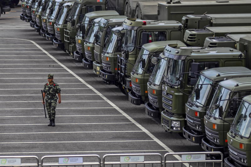 A member of armed police walks next to trucks in Shenzhen near Hong Kong.