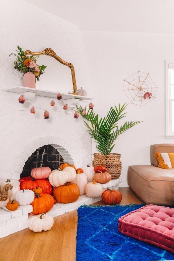 """<p>If you have a non-functioning fireplace, fill it with the symbol of the season for a fast, easy, but totally charming fall look. Include a simple garland, like this one made from tassels in autumn colors, and a few mini pumpkins on the mantel, and you've got decor that can go all season long! If you want to Halloween it up, a spider and web on a nearby wall makes for an cute addition.</p><p><strong>See more at <a href=""""https://studiodiy.com/our-halloween-home-tour/"""" target=""""_blank"""">Studio DIY</a>.</strong></p>"""