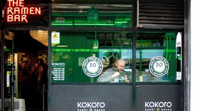 Seorang pria menyantap hidangan dalam sebuah bar yang kembali buka di Dublin, Irlandia, Senin (29/6/2020). Irlandia memasuki fase ketiga pencabutan pembatasan COVID-19, dengan mengizinkan lebih banyak bisnis kembali beroperasi dan memberikan kebebasan pergerakan lebih besar kepada masyarakat. (Xinhu