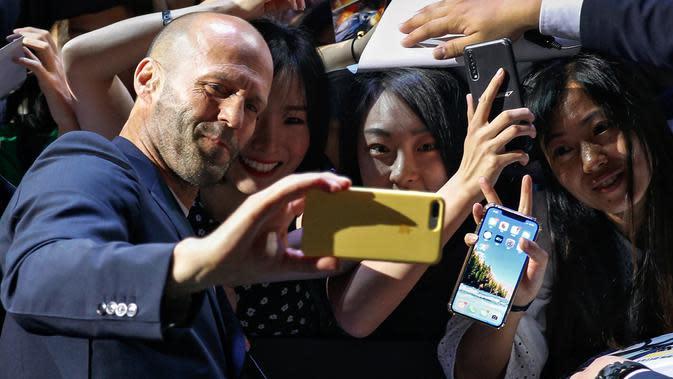 Aktor Jason Statham berswafoto bersama penggemar selama acara red carpet dalam premiere film 'Fast & Furious: Hobbs & Shaw' di Beijing, China, Senin (5/8/2019). Hobbs and Shaw menempatkan dua aktor laga papan atas, Jason Statham dan Dwayne Johnson sebagai pemeran utama. (AP Photo/Andy Wong)