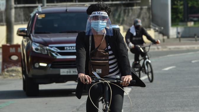 Pekerja kantor mengenakan pelindung saat mengendarai sepedanya di Manila pada 20 Mei 2020. Penjualan sepeda meroket menyentuh 300-500 unit dalam dua hari sejak pemerintah Filipina mulai melonggarkan langkah-langkah karantina yang dilakukan untuk mencegah penyebaran pandemi COVID-19. (Ted ALJIBE/AFP)