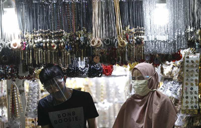 Accessories venders wearing face mask wait customers amid fears of the new coronavirus outbreak at a market in Jakarta, Indonesia Tuesday, June 30, 2020.(AP Photo/Achmad Ibrahim)