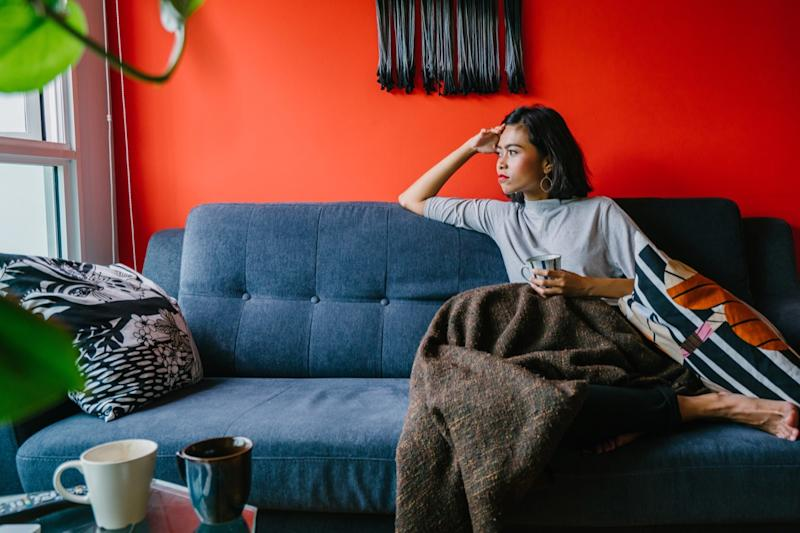 Woman looking out the window on a couch