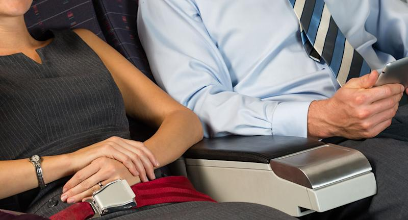 A Qantas flight attendant says armrests are meant to be shared, even if you are sitting in the middle seat. Pictured is a stock of a man and a woman sharing a plane armrest.