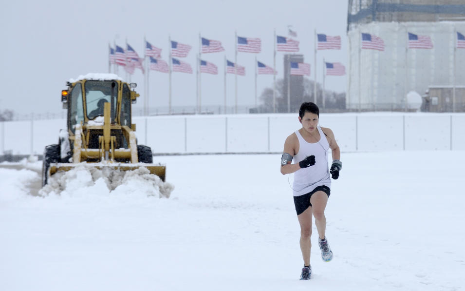 Snow is plowed behind a jogger running on the Washington Monument grounds in Washington, Monday, March 17, 2014. Snow has been falling in parts of the Mid-Atlantic and Northeast as winter-weary motorists faced another potentially treacherous commute Monday morning, just days before the start of spring. (AP Photo/Susan Walsh)