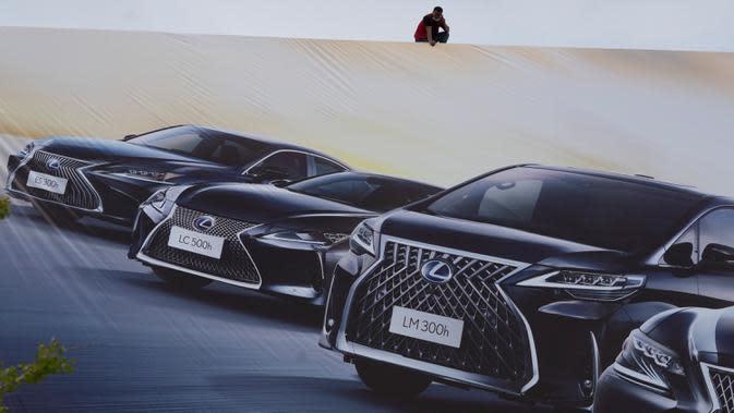 Seorang pekerja mengawasi papan iklan untuk pameran Auto China 2020 yang akan digelar di Beijing, Kamis (24/9/2020). Menandai bangkitnya kembali industri otomotif negara dengan penduduk terbanyak di dunia ini, China mengumumkan siap menggelar Auto China 2020. (AP Photo/Ng Han Guan)