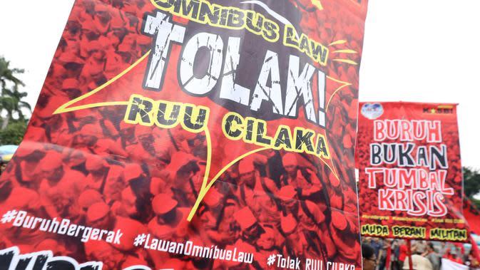 Poster bertuliskan tuntutan terlihat saat buruh yang tergabung dalam Gerakan Buruh Bersama Rakyat (Gebrak) berdemonstrasi di depan Gedung DPR, Jakarta, Senin (13/1/2020). Massa menyuarakan penolakan mereka terhadap Omnibus Law Rancangan Undang-Undang Cipta Lapangan Kerja. (Liputan6.con/Johan Tallo)