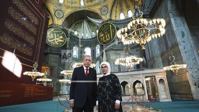 Turkey's President Recep Tayyip Erdogan, accompanied by his wife Emine, poses for photographs as he visits the Byzantine-era Hagia Sophia (Turkish Presidency via AP, Pool)
