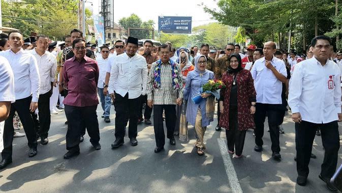 Mantan Wakil Presiden Jusuf Kalla atau JK didampingi istrinya Mufidah berjalan kaki saat tiba di kampung halamannya, Makassar, Sulawesi Selatan, Sabtu (26/10/2019). Beragam pertunjukan ditampilkan saat JK dan rombongan berjalan. (Liputan6.com/HO/Tim JK)