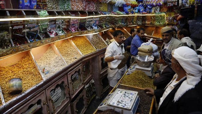 Warga membeli kacang-kacangan dan makanan manis di sebuah pasar menjelang Hari Raya Idul Fitri di Sanaa, Yaman, Jumat (22/5/2020). Idul Fitri menandai berakhirnya bulan suci Ramadan. (Xinhua/Mohammed Mohammed)