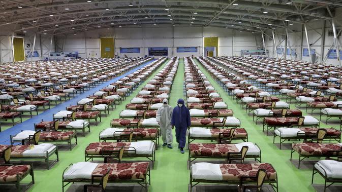 Petugas berpakaian pelindung berjalan melewati deretan tempat tidur di rumah sakit sementara khusus pasien virus corona COVID-19 di Teheran, Iran, Kamis (26/3/2020). Rumah sakit sementara ini dibangun oleh tentara Iran. (AP Photo/Ebrahim Noroozi)
