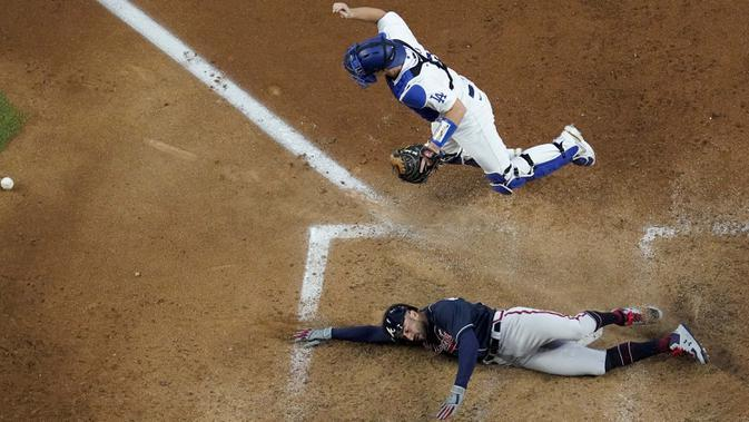 Pemain Atlanta Braves Nick Markakis mencetak gol melewati penangkap Los Angeles Dodgers Will Smith dengan dua gol oleh Cristian Pache selama inning kelima dalam Game 2 dari Seri Kejuaraan Liga Nasional bisbol di Arlington, Texas, Selasa (13/10/2020). (AP Photo/David J. Phillip)