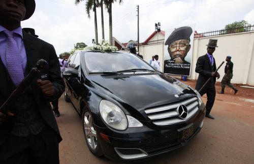 """A hearse carrying the coffin of late author Chinua Achebe at his funeral service, held at St. Philip's Anglican Church in Ogidi, Nigeria, Thursday, May 23, 2013. Writer Chinua Achebe shunned Nigeria's corrupt politicians and twice turned down national honors, never fearing to criticizing those he felt ruined a country he once supported breaking away from. On Thursday, however, the lawmakers and the country's elite came to him. Hundreds attended Achebe's funeral among the rolling hills of his eastern Nigeria home, a service that saw even President Goodluck Jonathan literally hold up the writer's books. The gold plaque on his coffin simply called him the """"eagle atop the Iroko tree"""" in his native Igbo language. (AP Photo/Sunday Alamba)"""