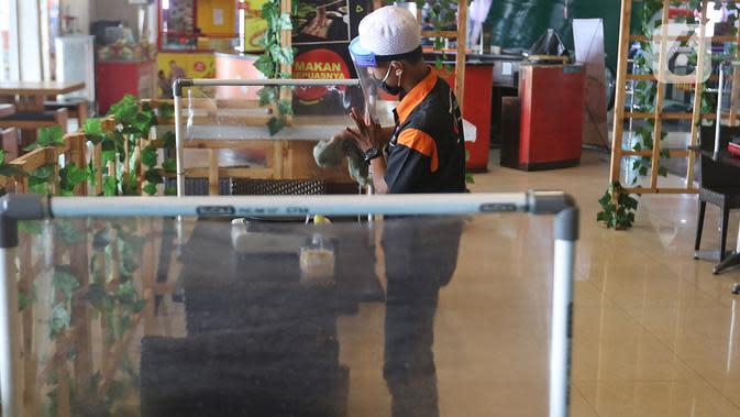 Petugas membersihkan pembatas plastik di salah satu restoran Mall Bekasi, Jawa Barat, Minggu (7/6/2020). Sejumlah tempat makan mulai menerapkan protokol kesehatan untuk pengunjung yang makan ditempat untuk mencegah penyebaran wabah COVID-19. (Liputan6.com/Herman Zakharia)