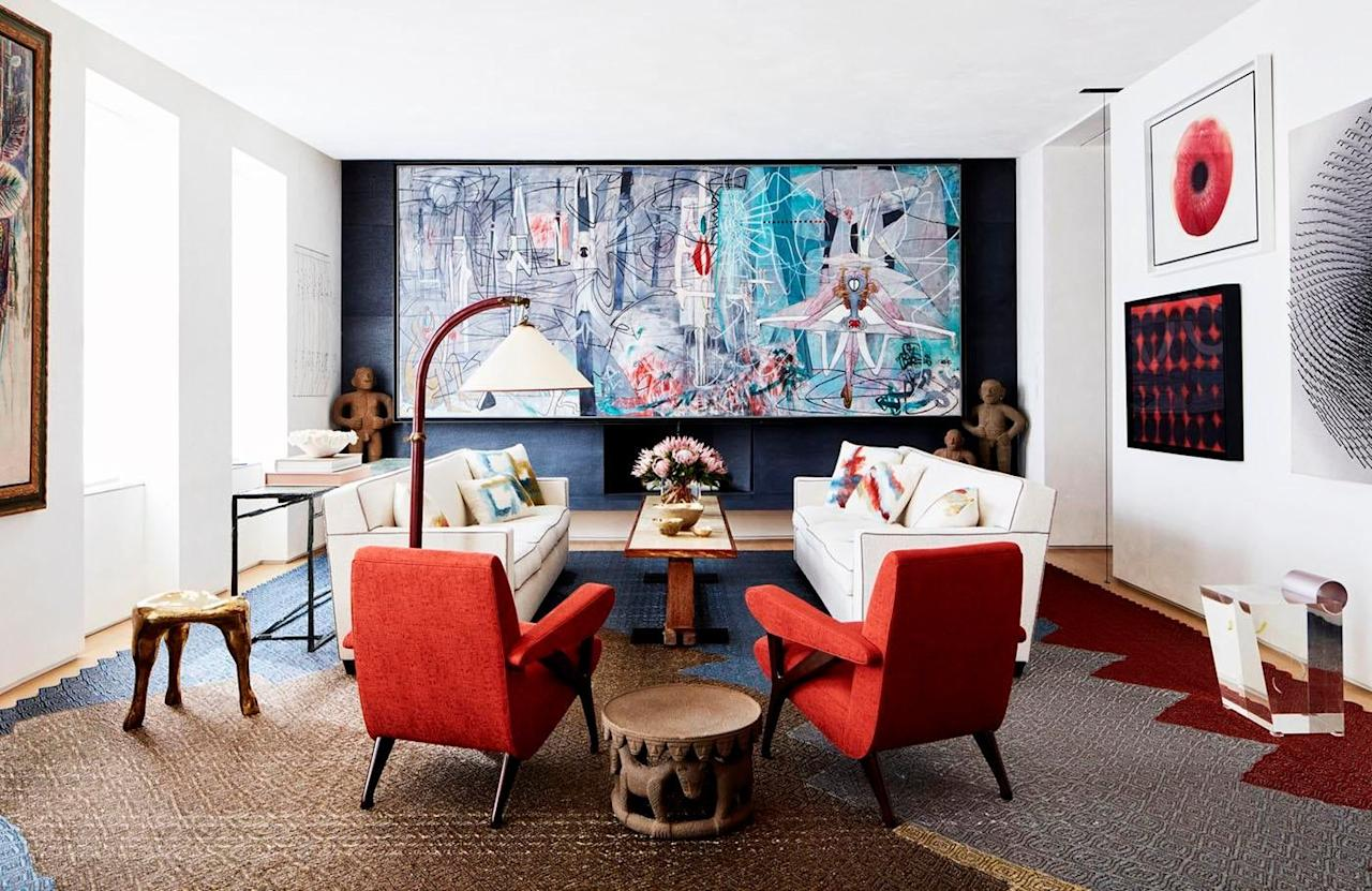 """<p>A colorful canvas enlivens this vibrant room with bright red armchairs designed by <a href=""""https://www.chairish.com/shop/amy-lau-design"""" target=""""_blank"""">Amy Lau Design</a>.</p>"""