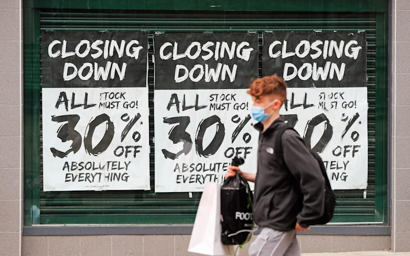 Man with face mask walks in front of a high street shop with a closing down notice in the window as coronavirus continues to hurt retailers - Mike Egerton/PA