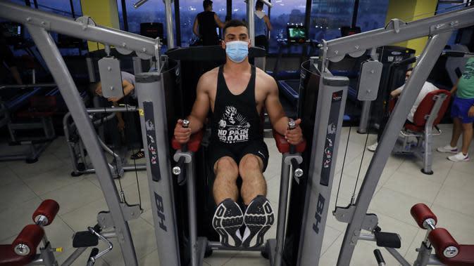Seorang pria mengenakan masker saat berolahraga di pusat kebugaran Kota Hebron, Tepi Barat, Palestina, Kamis (6/8/2020). Kementerian Kesehatan Palestina mendesak warga mematuhi langkah-langkah kesehatan setelah pemerintah melonggarkan kebijakan pencegahan COVID-19. (Xinhua/Mamoun Wazwaz)