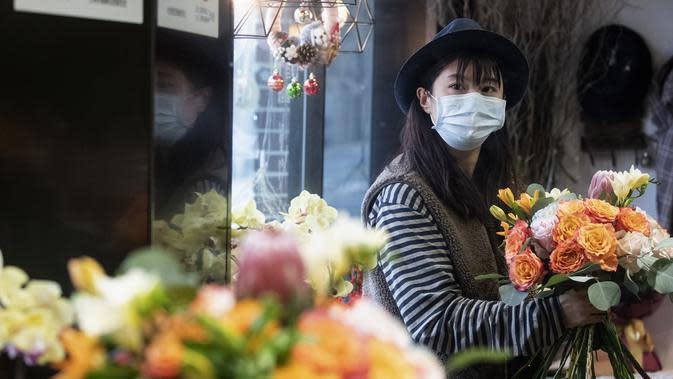 Penjual bunga Zhao Yuanyuan mengenakan masker mengatur bunga menjelang Hari Valentine di tokonya di Shanghai (12/2/2020). Pasangan-pasangan yang merayakan Hari Valentine di seluruh China dibayangi wabah virus corona COVID-19. (AFP Photo/Noel Celis)
