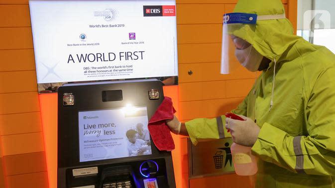 Petugas membersihkan mesin ATM di kantor DBS Tower, Jakarta, Selasa (30/6/2020). Bank DBS Indonesia menerapkan protokol kesehatan dengan penyemprotan cairan desinfektan dan melakukan pelapisan antimicrobial di area kantor untuk mencegah penyebaran virus Covid-19. (Liputan6.com/Fery Pradolo)