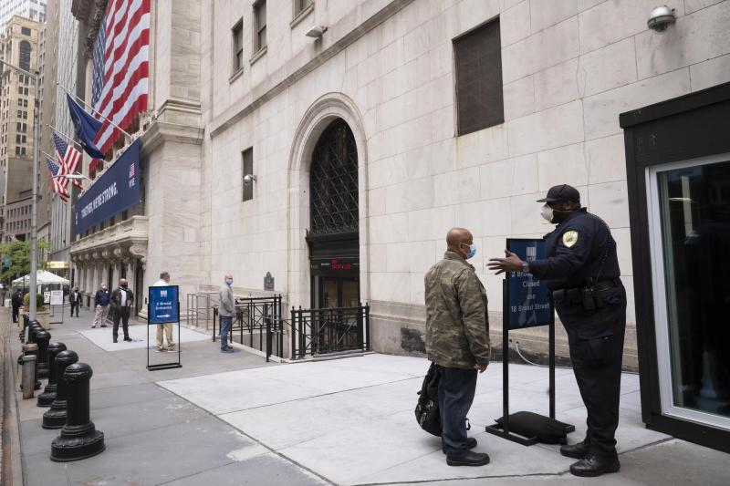 New York Stock Exchange employees wait to enter the building as the trading floor partially reopens, Tuesday, May 26, 2020. (AP Photo/Mark Lennihan)