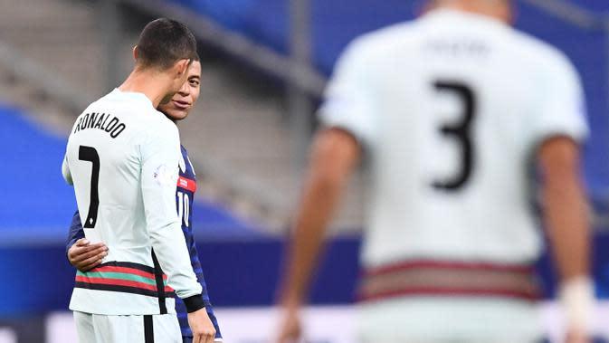 Striker Portugal, Cristiano Ronaldo, berbincang dengan striker Prancis, Kylian Mbappe, pada laga UEFA Nations League di Stadion Stade de France, Senin (12/10/2020). Kedua tim bermain imbang 0-0. (AFP/Franck Fife)