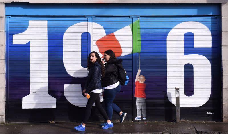 FILE PHOTO: Women walk past a mural marking the 100 year anniversary of the Irish Easter Rising in Dublin, Ireland