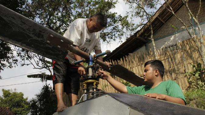 Gambar yang diambil pada 17 November 2019, Jujun Junaedi (kiri) menyelesaikan pembuatan helikopter buatannya di halaman belakang rumahnya di Sukabumi. Jujun merogoh kocek hingga lebih dari RP 30 juta rupiah untuk merakit helikopter bermesin genset dua silinder 700 cc ini. (Wulung WIDARBA/AFP)