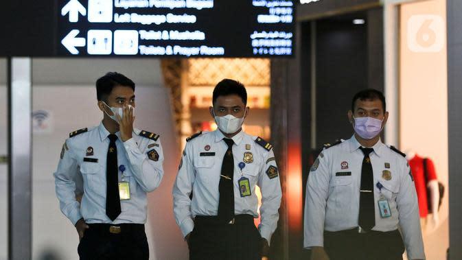 Petugas Imigrasi bandara menggunakan masker pelindung saat berada di Pintu Kedatangan Terminal 3 Ultimate Bandara Soekarno Hatta, Tangerang, Jumat (31/1/2020). Hal itu dilakukan sebagai antisipasi penularan dan penyebaran virus corona (2019-nCov). (Liputan6.com/Johan Tallo)