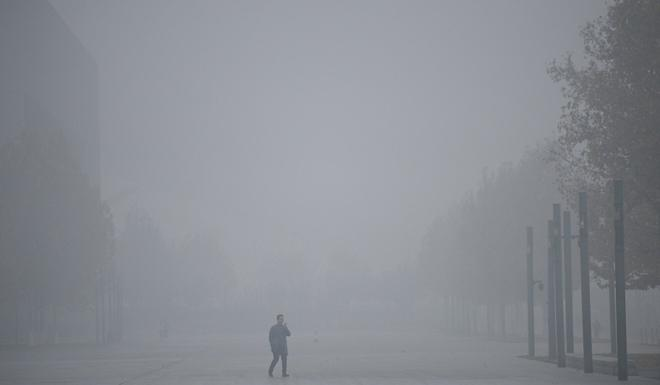 A man uses his mobile phone as he walks through smog in Tianjin, mainland China in 2018. Photo: Reuters
